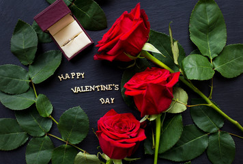 """The inscription """"Happy Valentine"""" on a black background with red roses and wedding ring"""