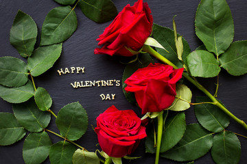 """The inscription """"Happy Valentine"""" on a black background with red roses"""