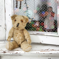 Vintage teddy-bear sitting on the wardrobe