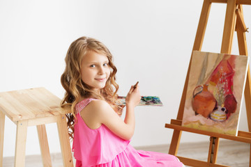 Portrait of a lovely little girl painting a picture in a studio