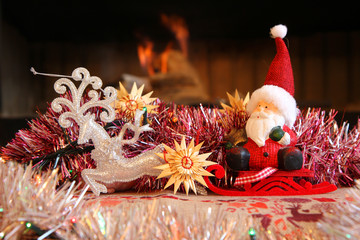 Santa Claus is sitting on the red sleigh pulled by reindeer with a fireplace on the background