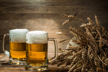 Two mugs of beer next to spikelets of wheat