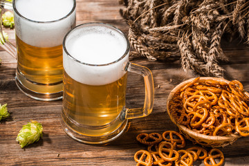 Mugs frothy beer, hops, pretzels and wheat on wooden table