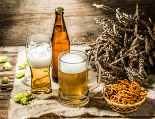 Mug, glasse, bottle of beer with foam on cloth and pretzels