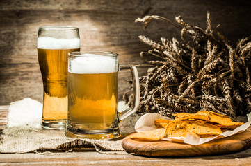 Mug, glass of beer with wheat spikelets and potato chips