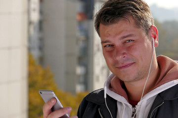 Man using smartphone on balcony during the sunny day