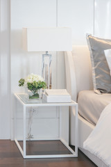 Flower jar, book and reading lamp on white frame bedside table next to bed in modern interior bedroom