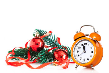 X-mas festive wallpaper. Alarm clock showing midnight and branch of Christmas tree decorated with two red balls and ribbons.