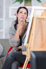 thoughtful pretty young woman artist thinking near her painting