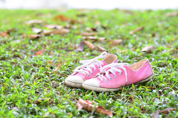Pink sneakers on a green grass. Rest in the park without shoes.