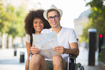 disabled man and girlfriend tourists consulting map of city