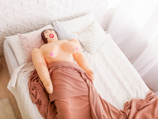 Sex doll lies under blanket on bed.