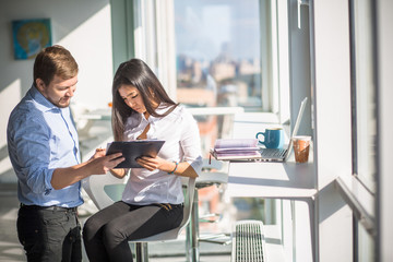 Businessman and businesswoman looking at documentation of new business plan or strategy while working in office interior. Buisiness concept.