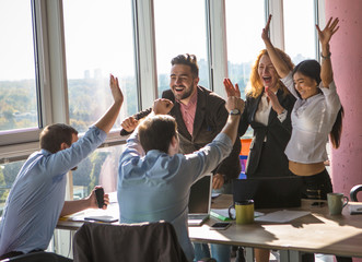 Business people showing team work all together in office interior. Colleagues or workers giving five to each other after concluding agreement or contract between companies. Wall mural