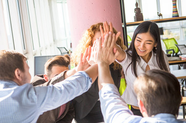 Business colleagues giving five to each other after signing agreement or contract between companies or enterprises. Workers showing team work in office.