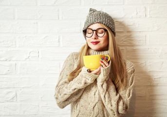 Romantic Winter Hipster Girl in Knitted Sweater and Beanie Hat Enjoying a Cup of Hot Tea or Coffee in Hands. Lovely Dreaming Woman. White Brick Wall Background. Toned Photo with Copy Space.