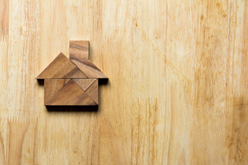 Wooden tangram puzzle in home shape for dream home or happy life