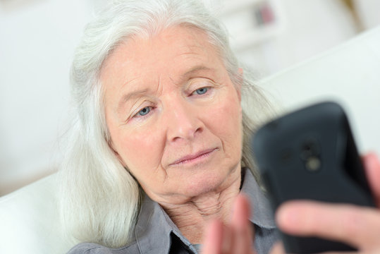 elderly woman sends sms on mobile phone