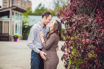 A pregnant young woman and her husband. A happy family standing at the red autumn hedge, holding belly. pregnant woman relaxing in the park.