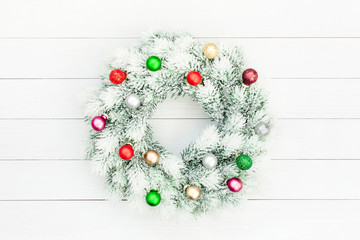 Decorated Christmas wreath  on white wooden background. Copy space, top view