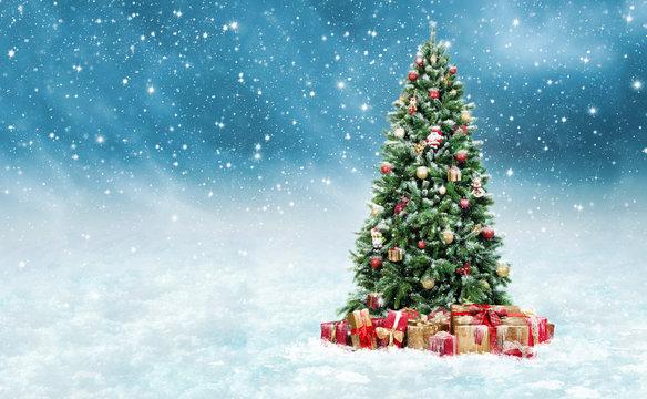 Geschmückter Christbaum mit Geschenken im Schnee