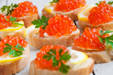 Red caviar on bread with lemon and parsley