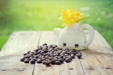 Coffee beans on grunge wood background with Ixora flower pot and