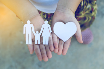Children hands holding small model of heart and family , concept