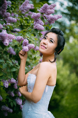 Portrait of young pretty bride surrounded by lilac