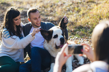 Woman takes a photo of young couple enjoying together with their Saint Bernard puppy .