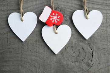 Decorative white wooden Christmas hearts and red mitten on grey rustic wooden background with copy space.Selective focus.Winter holidays,Merry Christmas or Happy New Year concept.