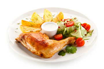 Grilled chicken legs with chips and vegetables isolated on white background