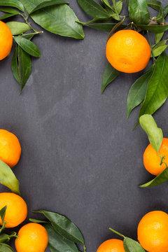 Tangerine fruits on dark table