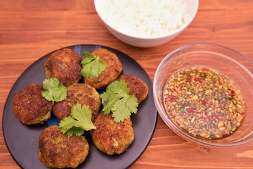 Asian, thai or vietnam style fish and vegetable burgers or fritters with fresh coriander leaves served with boiled rice and homemade fresh sweet chili sauce consist from chili, cucumber, soy sauce.