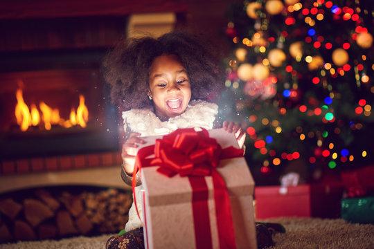 girl opening Christmas magic presents.