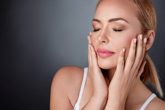middle aged woman touching her face perfect skin
