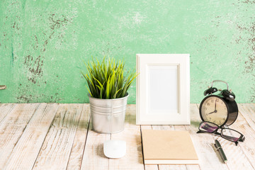 Wooden workplace desktop with clock; plants; glasses; Frame and notebook