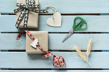 Boxes, gift ribbons, shape wooden heart and scissors on blue wooden hand painting time of preparation for Christmas. Subject capture against soft windows lighting.