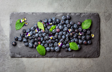 Berry blueberry with fresh mint leaves, edible flowers slate background