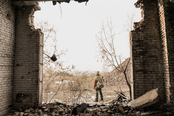 young boy stands with a gun in his hand. wanderer in the world of the apocalypse. boy in a protective cloak and hood. child standing near the destroyed building. a child soldier. young boy soldiers.