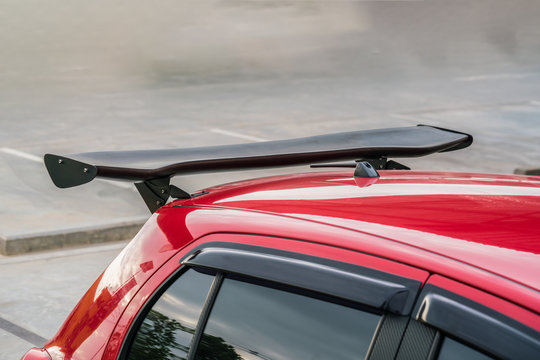 Car part ; Close up detail of a custom racing carbon fiber spoiler on the rear of a modern car with copy space