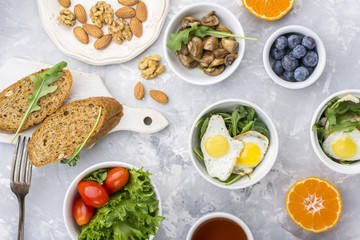 Healthy breakfast with fried eggs, fresh bread, salad, berries, tomatoes, nuts, beverage cup, arugula,  mushrooms on a gray light background. Top view