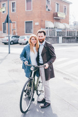 Couple of young beautiful blonde and redhead woman and man posing outdoor in back light holding a bicycle - happiness, smiling, transport concept