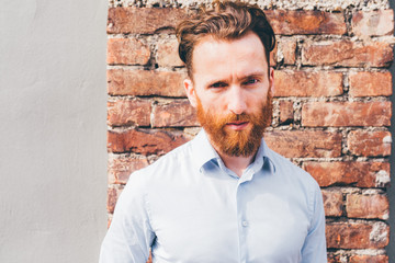 Portrait of young beautiful redhead millennial man posing outdoor in back light, looking in camera serious - pensive, thoughtful, thinking future concept
