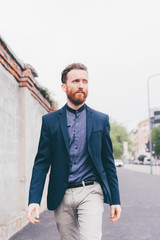 Young handsome caucasian bearded redhead millennial man walking outdoor in the city, overlooking, serious - pensive, thoughtful, thinking future concept