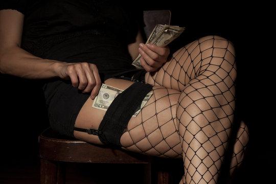 hooker in fishnet stockings counts money