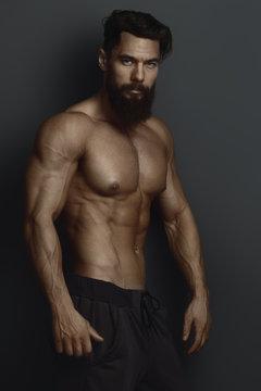 bearded bodybuilder against the dark wall