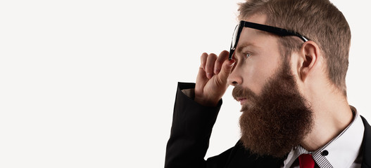 Close up portrait of big bearded european guy in eye glasses. Side view on engineer with thinking emotion. Copy space for text or another content.