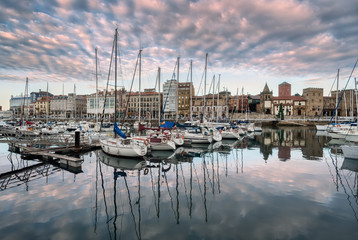 Yatchs and pier in leisure port on maritime fishing district of Gijon, Spain, Europe. Beautiful reflection on calm sea water of boats, buildings, sky at dusk at touristic cultural travel destination. Wall mural