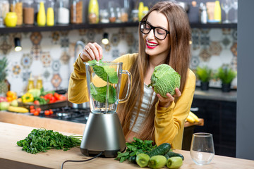 Young smiling woman making smoothie with fresh greens in the blender in kitchen at home. Healthy vegetarian smoothie for weight loss and detox